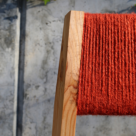 close up wooden chair with red wool backrest