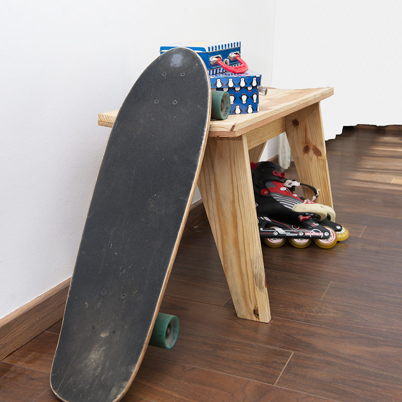 wooden bench with a skateboard leaning against it