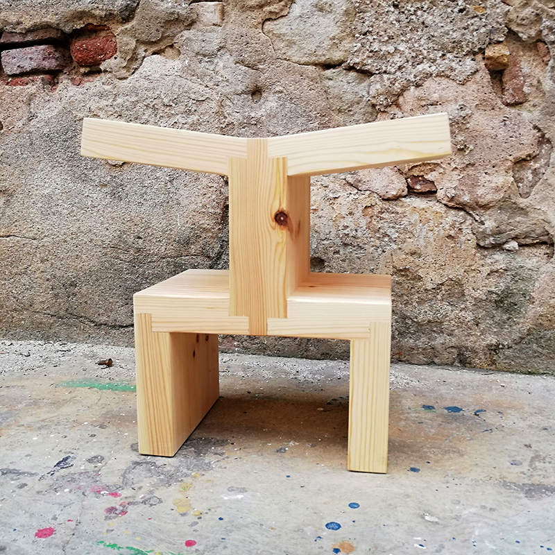single wooden stool in front of old wall